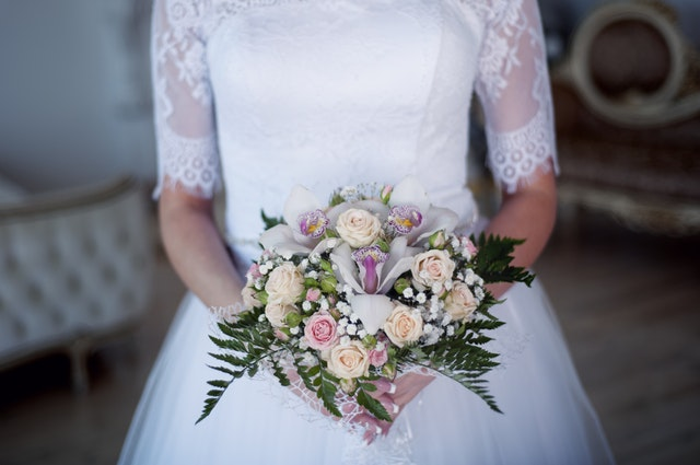 an image of a bride in a white wedding dress holding an assorted bouquet